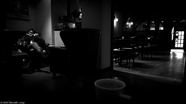 woman in a chair in a dark cafe reading a book from Caribbean book selections