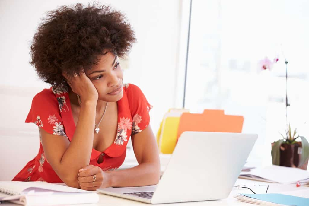 Frustrated Woman Working At Desk trying to improve focus
