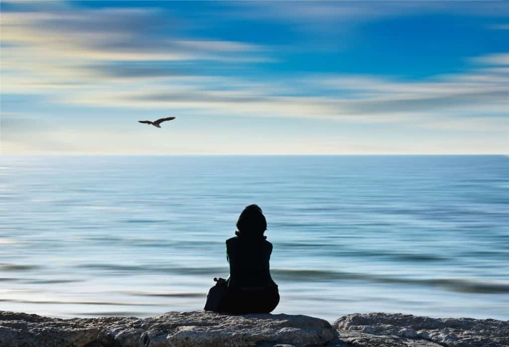 woman sitting in front of an ocean